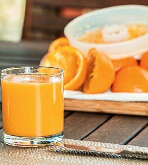 Friskpresset juice med appelsiner i baggrunden