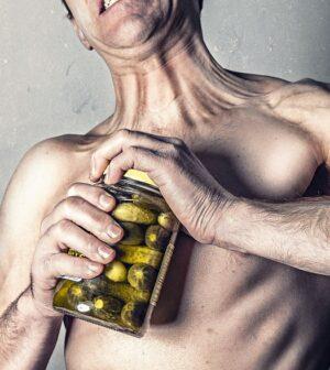 Mand har problemer med at åbne låg på syltede agurker